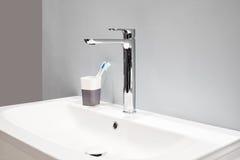 豪华高龙头搅拌器和牙刷在一块玻璃在一个白色水槽在一个美丽的灰色卫生间里 库存图片
