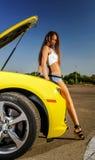 豪华魅力女孩和黄色跑车 免版税库存照片