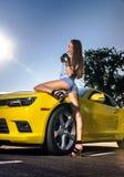 豪华魅力女孩和黄色跑车 库存图片