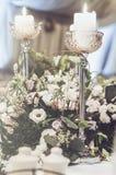 豪华宴会桌设置了与花奶油色玫瑰的富有的装饰,桃红色康乃馨,高白色的南北美洲香草,典雅的蜡烛 免版税库存照片
