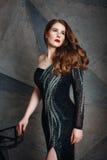 豪华黑礼服的年轻红色头发妇女 免版税库存照片