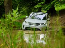 豪华SUV 4x4 roading通过池塘 免版税库存照片
