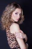 豹子礼服的美丽的性感的女孩在明亮的构成在黑背景的演播室 免版税库存照片