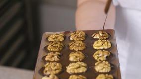 贝克的手由液体巧克力倾吐与一半的巧克力candys核桃以形式 股票视频