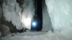 贝加尔湖冰洞的旅行人  旅行到冬天海岛 背包徒步旅行者是走冰洞穴 旅客看 股票视频