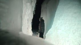 贝加尔湖冰洞的旅行人  旅行到冬天海岛 背包徒步旅行者是走冰洞穴 旅客看 影视素材
