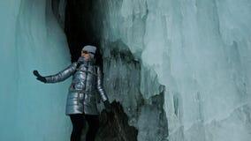 贝加尔湖冰洞的旅行妇女  旅行到冬天海岛 女孩背包徒步旅行者是走冰洞穴 旅客神色 股票录像