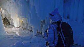 贝加尔湖冰洞的旅行妇女  旅行到冬天海岛 女孩背包徒步旅行者是走冰洞穴 旅客神色 影视素材