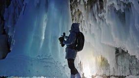 贝加尔湖冰洞的旅行妇女  旅行到冬天海岛 女孩背包徒步旅行者是走冰洞穴 旅客神色 股票视频