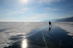 贝加尔湖冰镜子表面上的溜冰者在镇压和小丘之间的 免版税库存照片