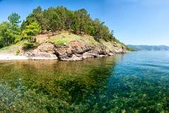 贝加尔湖在Bolshiye Koti,俄罗斯 高岸的水平的天视图,绿色森林,岩石,清楚的湖水 免版税库存照片