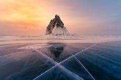 贝加尔湖结冰水湖有岩石山的和在日落天空背景以后 库存图片