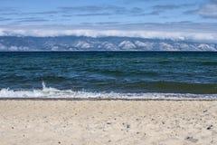 贝加尔湖蓝色波浪在西伯利亚在夏天是残破的反对在山背景的一个沙滩 免版税库存图片