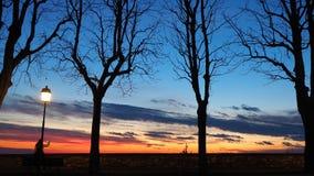 贝加莫,老城市 意大利伦巴第 敬佩往Po谷的日落从古老墙壁人的剪影 免版税库存图片