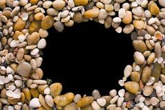贝壳和小卵石在黑背景,自然海滨石头 免版税库存照片