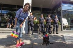 贝尔格莱德摆在与她的狗&一面快乐旗子的同性恋自豪日参加者在警察前面 游行今年发生了,不用麻烦 图库摄影