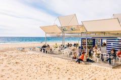 贝尼多姆,西班牙- 2018年1月14日:人休息,读书和下休息在公开贝尼多姆莱万特海滩的棋 图库摄影