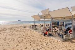 贝尼多姆,西班牙- 2018年1月14日:人休息,读书和下休息在公开贝尼多姆莱万特海滩的棋 免版税库存图片