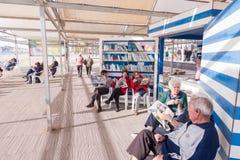 贝尼多姆,西班牙- 2018年1月14日:人休息,读书和在公开贝尼多姆莱万特海滩图书馆地区下棋 库存照片