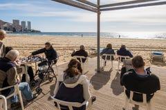 贝尼多姆,西班牙- 1月14 :人休息,读书和在公开贝尼多姆莱万特海滩图书馆地区下棋 免版税库存图片