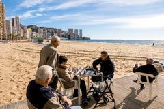 贝尼多姆,西班牙- 1月14 :人休息,读书和在公开贝尼多姆莱万特海滩图书馆地区下棋 库存图片