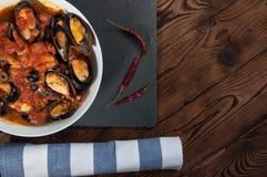 贝类海鲜 在西红柿酱的热的新鲜的意大利开胃蒸的淡菜用橄榄和红辣椒在葡萄酒木桌上 免版税图库摄影