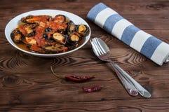 贝类海鲜 在西红柿酱的热的新鲜的意大利开胃蒸的淡菜用橄榄和红辣椒在葡萄酒木桌上 库存图片