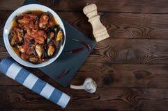 贝类海鲜 在西红柿酱的热的新鲜的意大利开胃蒸的淡菜用橄榄和红辣椒在葡萄酒木桌上 免版税库存照片