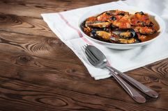 贝类海鲜 在西红柿酱的热的新鲜的意大利开胃蒸的淡菜用橄榄和红辣椒在葡萄酒木桌上 图库摄影