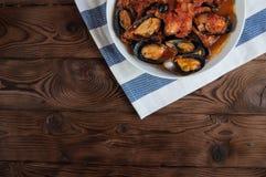 贝类海鲜 在西红柿酱的热的新鲜的意大利开胃蒸的淡菜用橄榄和红辣椒在葡萄酒木桌上 免版税库存图片