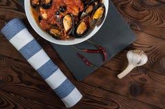 贝类海鲜 在西红柿酱的热的新鲜的意大利开胃蒸的淡菜用橄榄和红辣椒在葡萄酒木桌上 库存照片