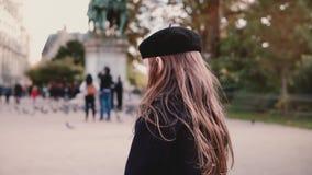 贝雷帽的小女孩在城市广场单独站立 回到视图 慢的行动 有仍然等待长的头发的女孩 股票录像