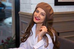 贝雷帽的美女在咖啡馆的窗口附近坐 库存照片