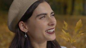 贝雷帽看看的滑稽的浪漫妇女太阳通过叶子 秋天公园 4K 股票录像