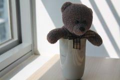 负担有坐由在阴影的窗口的杯子的玩具 免版税图库摄影