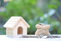 财务、堆硬币金钱和自然绿色背景、商业投资和不动产的式样房子 图库摄影
