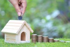 财务、堆硬币金钱和自然绿色背景、商业投资和不动产的式样房子 免版税库存照片