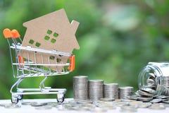 财务、式样房子和堆在微型手推车的硬币金钱在自然绿色背景,商业投资和真正 库存图片