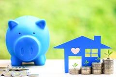 财务、蓝色房子硬币金钱模型和大头钉与蓝色的贪心在自然绿色背景、投资事务和银行业务 免版税库存图片