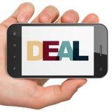 财务概念:拿着有成交的手智能手机在显示 免版税库存图片