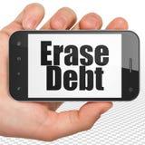 财务概念:递拿着智能手机以在显示的删掉债务 免版税库存照片