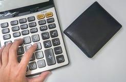 财务管理概念-在计算器的妇女手有金钱钱包的 免版税库存图片
