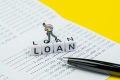 财政贷款、抵押或者债务概念,走微型商人的形象在与字母表大厦词贷款的立方体块  库存照片
