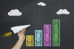 财政,事务,经济增长概念 在黑板的五颜六色的企业图用拿着飞机的手作为助力的标志 免版税库存照片