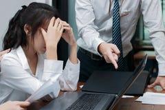 责备年轻亚裔妇女用手的恼怒的上司在面孔在办公室 免版税库存图片