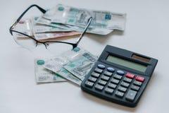 货币俄国 钞票五和一千卢布,背景,选择聚焦,在桌、玻璃和计算器上 库存图片