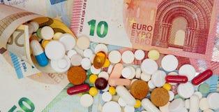 货币和药片 不同的颜色药片在金钱的 概念谎言医学货币集合听诊器 欧洲现金 免版税库存照片
