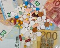 货币和药片 不同的颜色药片在金钱的 概念谎言医学货币集合听诊器 欧洲现金 免版税图库摄影