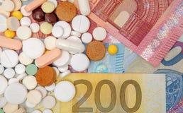 货币和药片 不同的颜色药片在金钱的 概念谎言医学货币集合听诊器 欧洲现金 库存图片