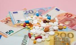 货币和药片 不同的颜色药片在金钱的 概念谎言医学货币集合听诊器 欧洲现金 库存照片